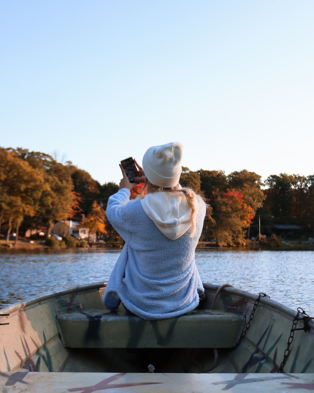 woman in white knit sweater and white knit cap sitting on boat during daytime
