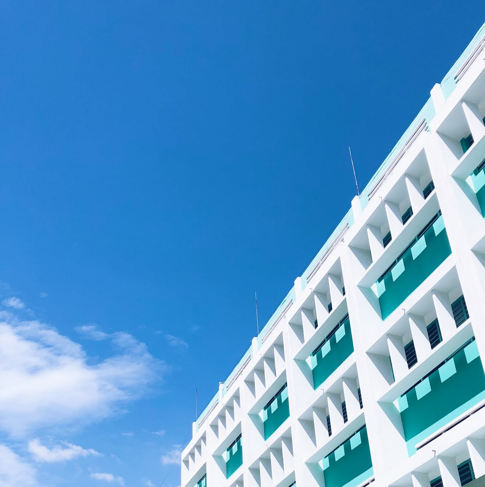 white and green concrete building under blue sky during daytime