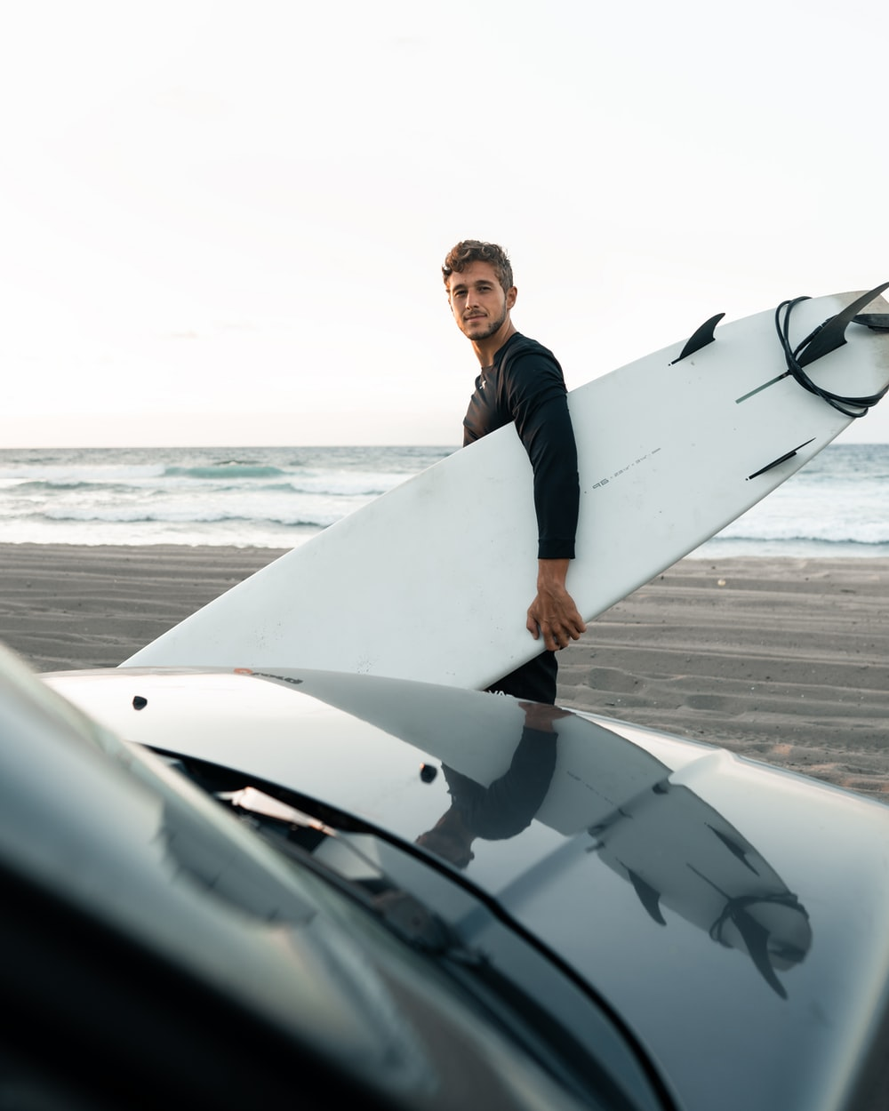 man in black suit holding white surfboard