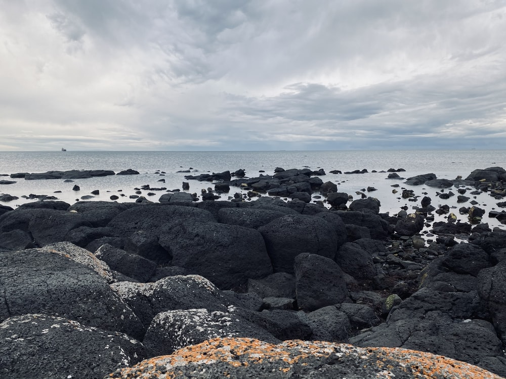 black and gray rocks on seashore under white clouds during daytime