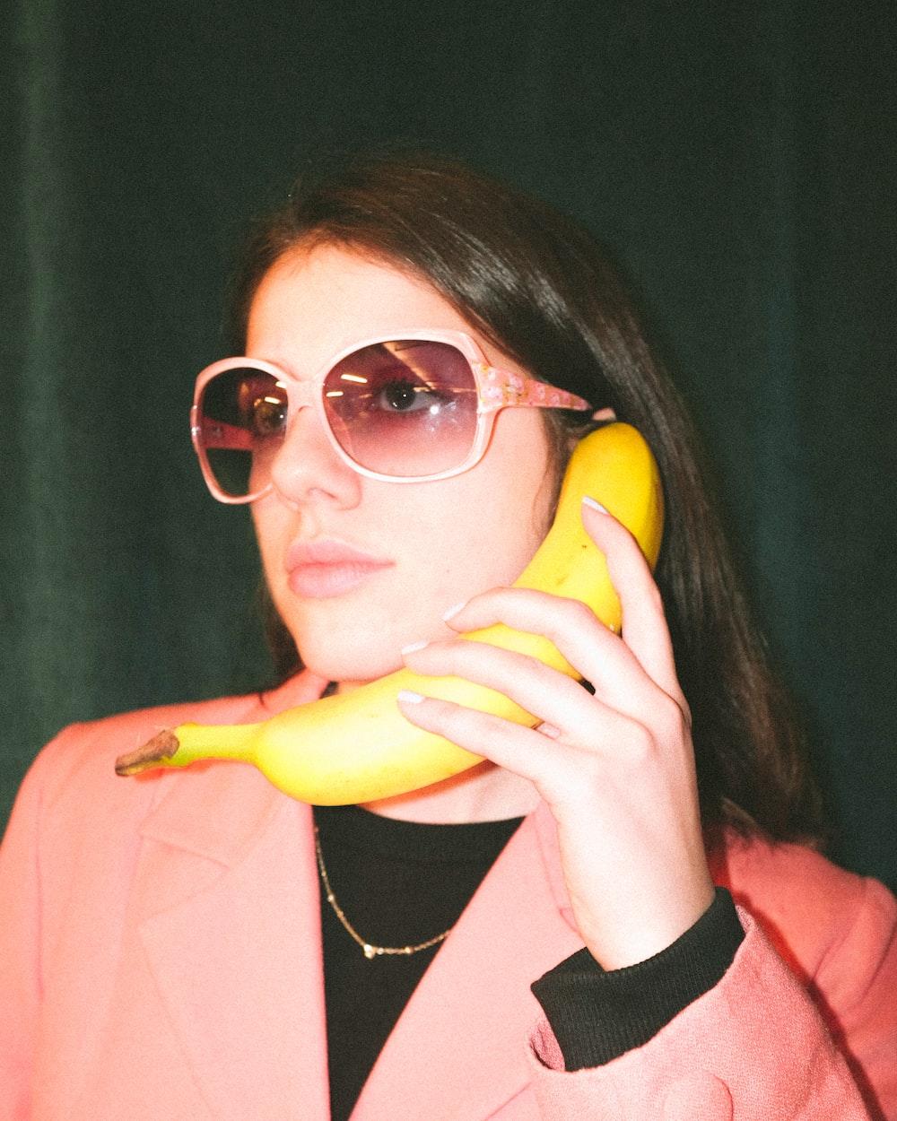woman in pink blazer holding yellow banana