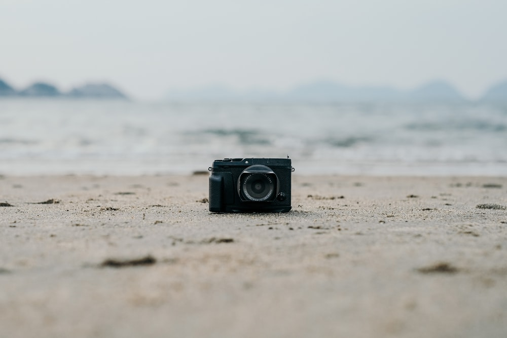 black camera on brown sand near sea during daytime