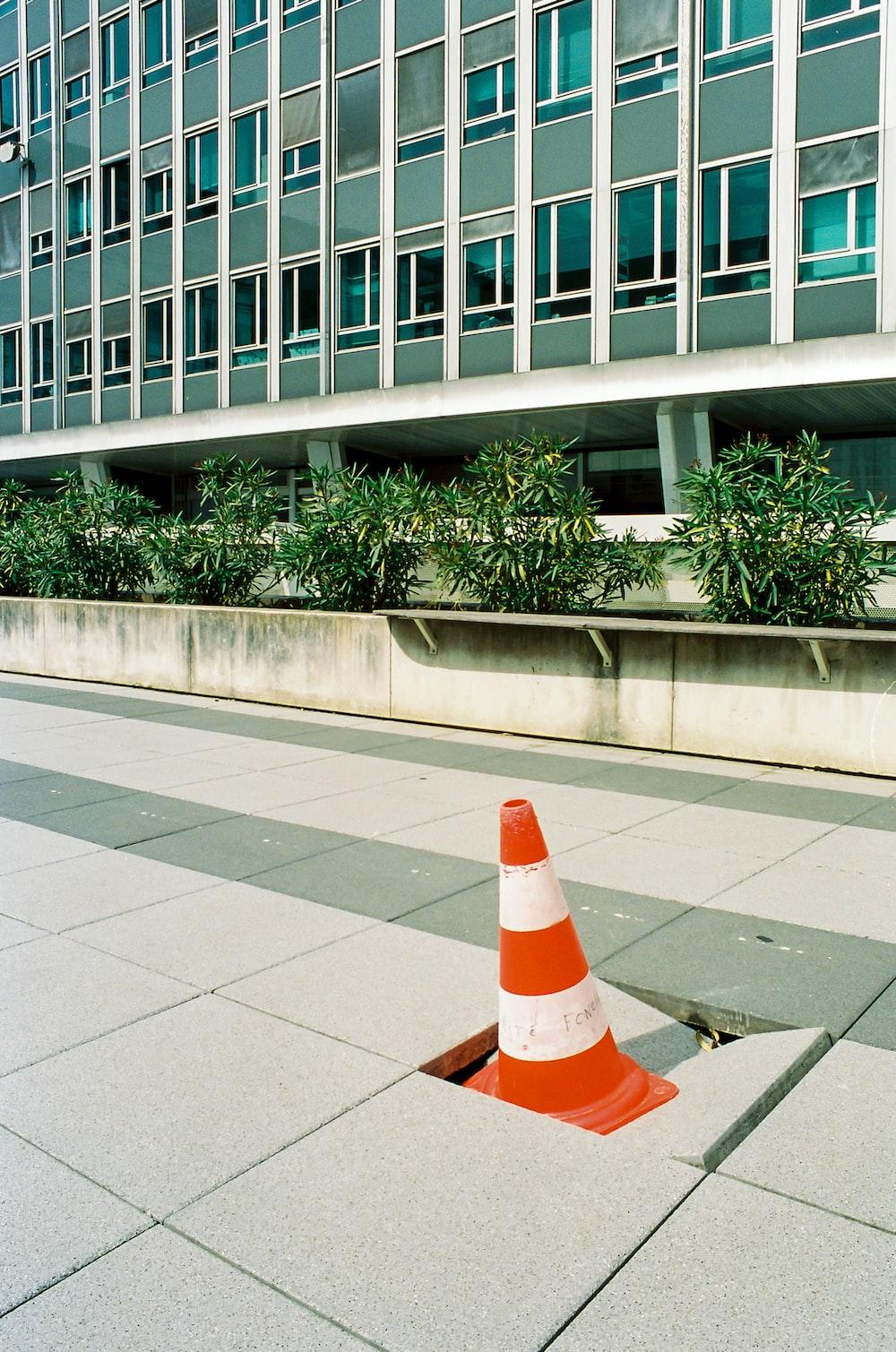 orange and white traffic cone on gray concrete floor