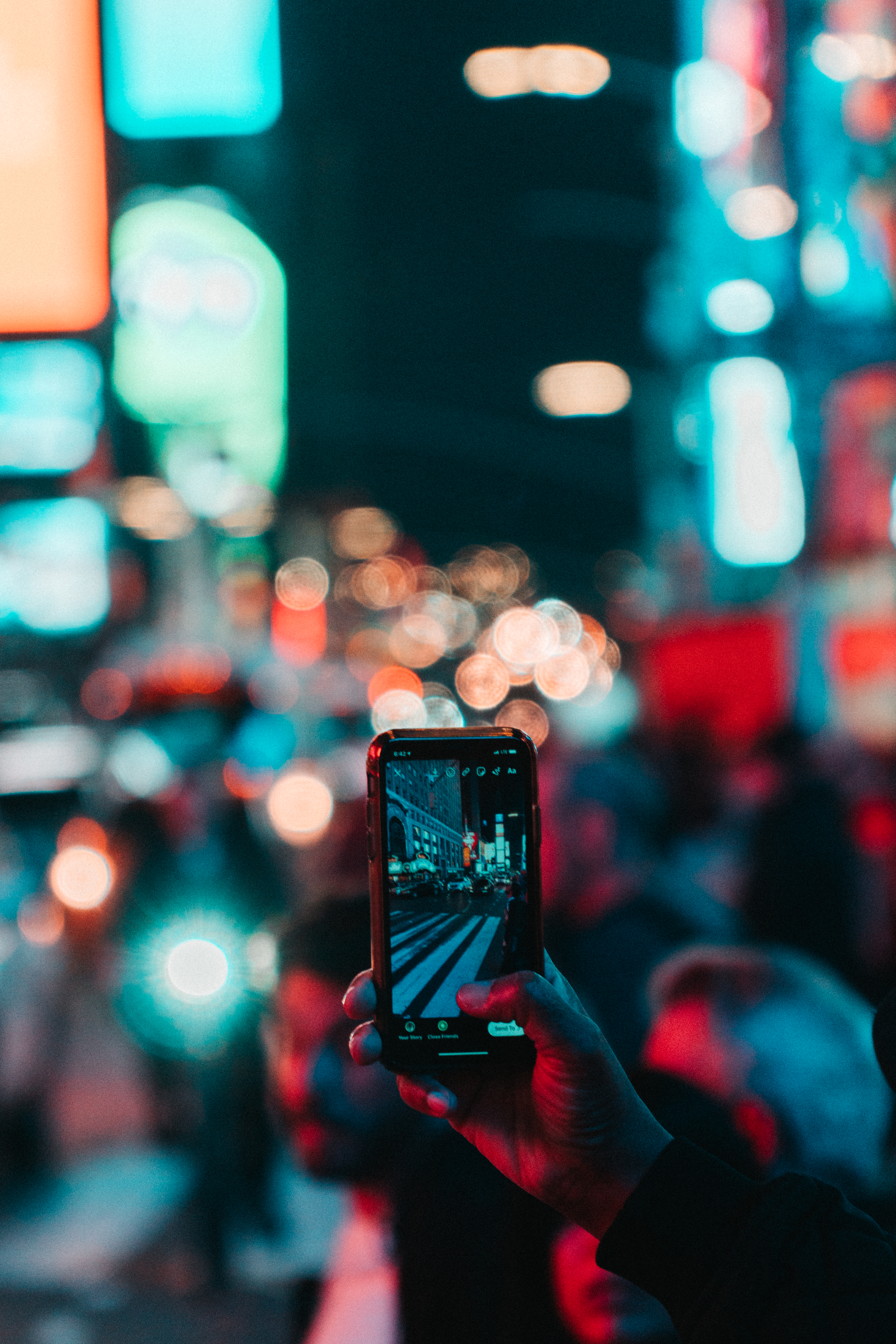 person taking photo of city during night time