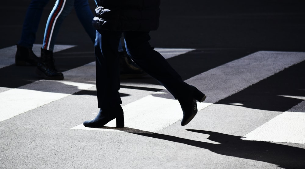 person in black pants and black shoes walking on gray asphalt road during daytime