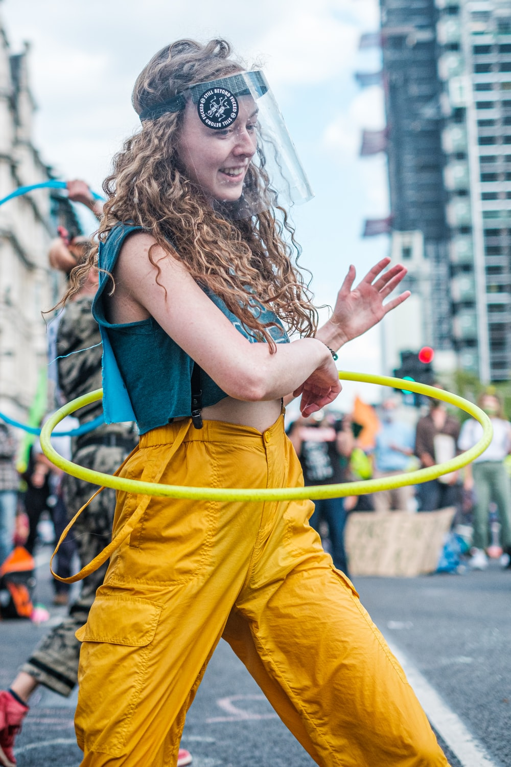 woman in blue tank top and yellow pants holding yellow rope