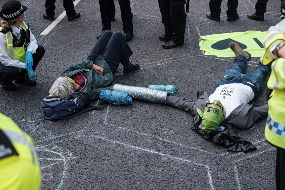 person in green and white jacket lying on gray concrete floor