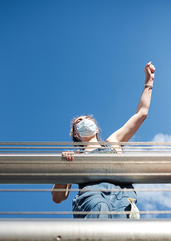 woman in blue denim jacket leaning on brown metal railings during daytime