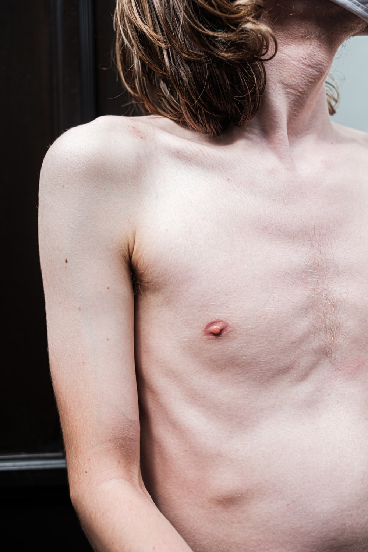 topless woman standing near black wall