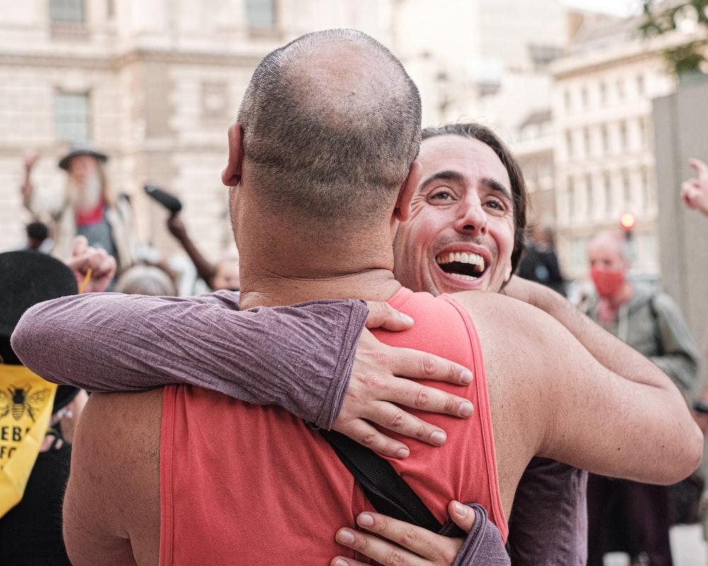 man in red tank top hugging man in gray long sleeve shirt