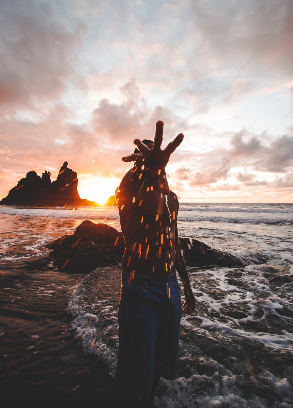 woman in black and white dress standing on seashore during sunset