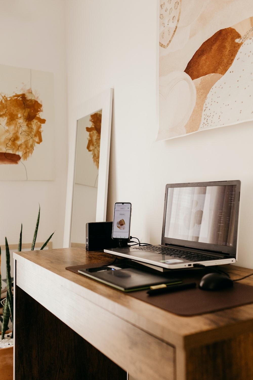 black laptop computer on brown wooden desk
