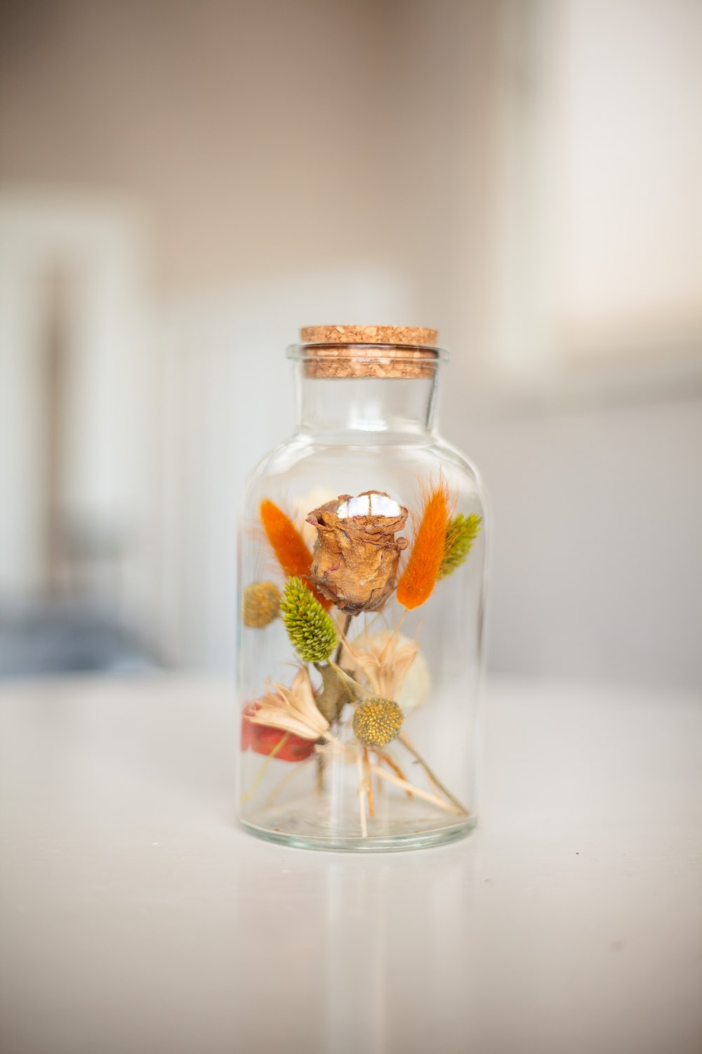 clear glass jar with green and red flower inside