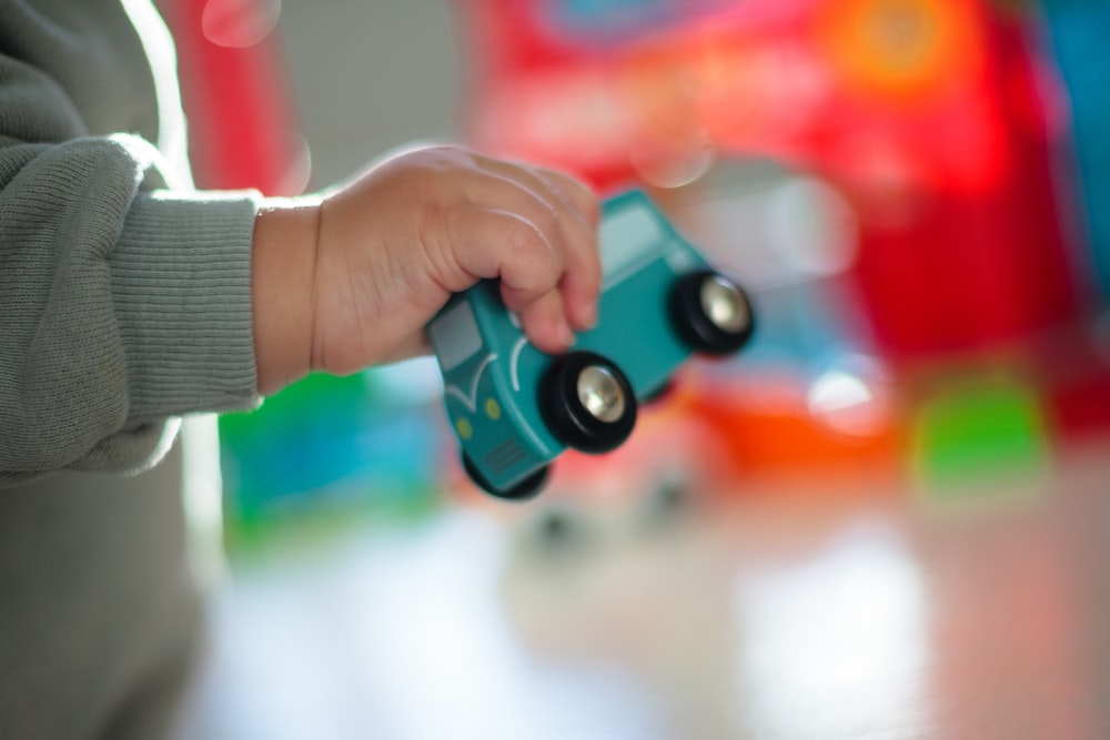 person holding blue and red toy gun