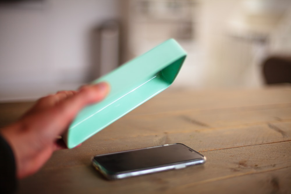 person holding teal plastic tool
