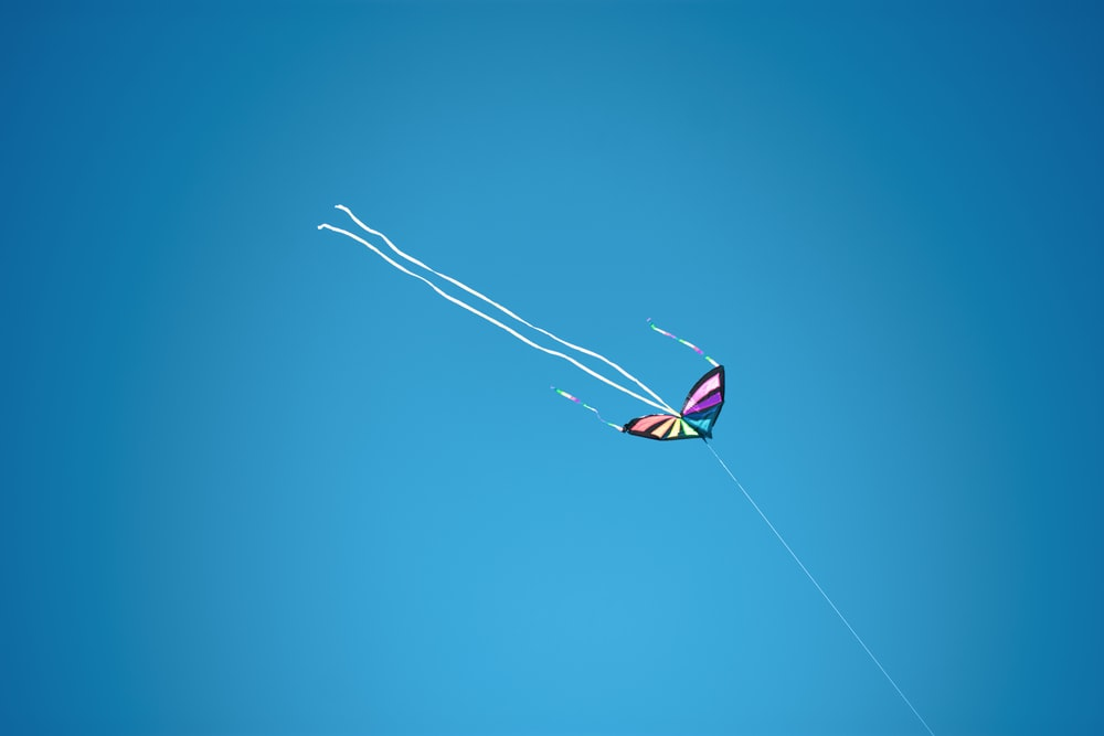 white red and blue kite flying in the sky