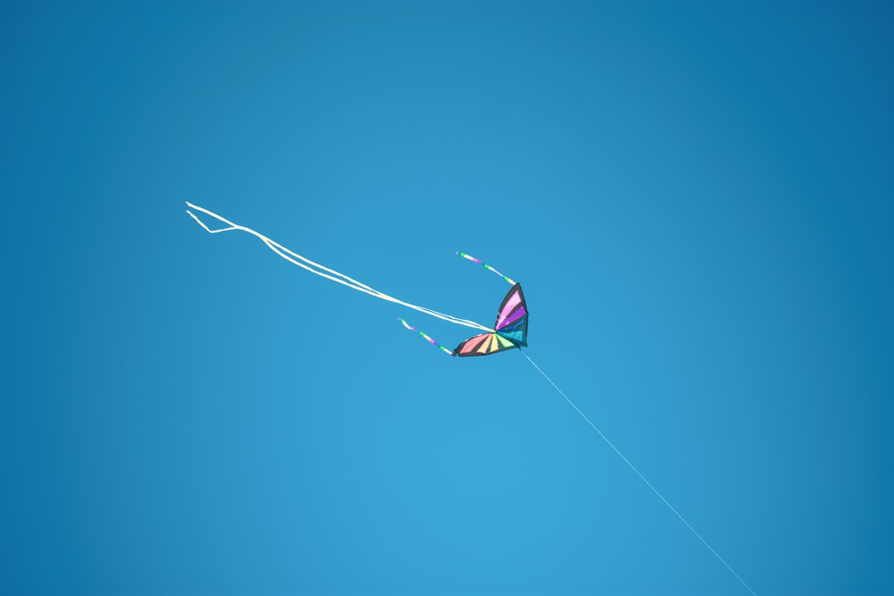pink yellow and blue kite flying on mid air under blue sky during daytime