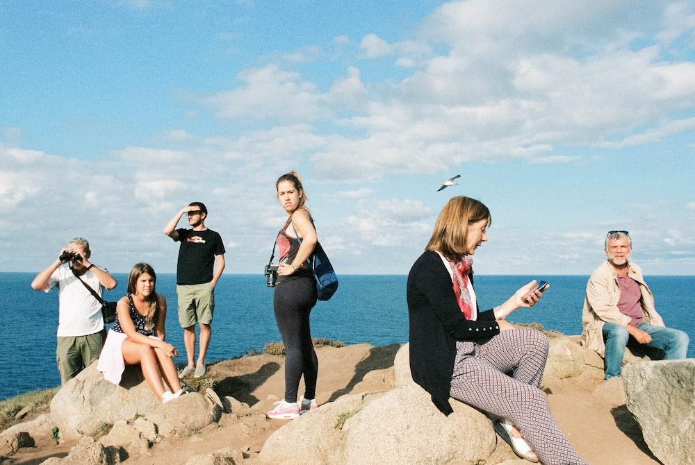 3 women sitting on rock near sea during daytime