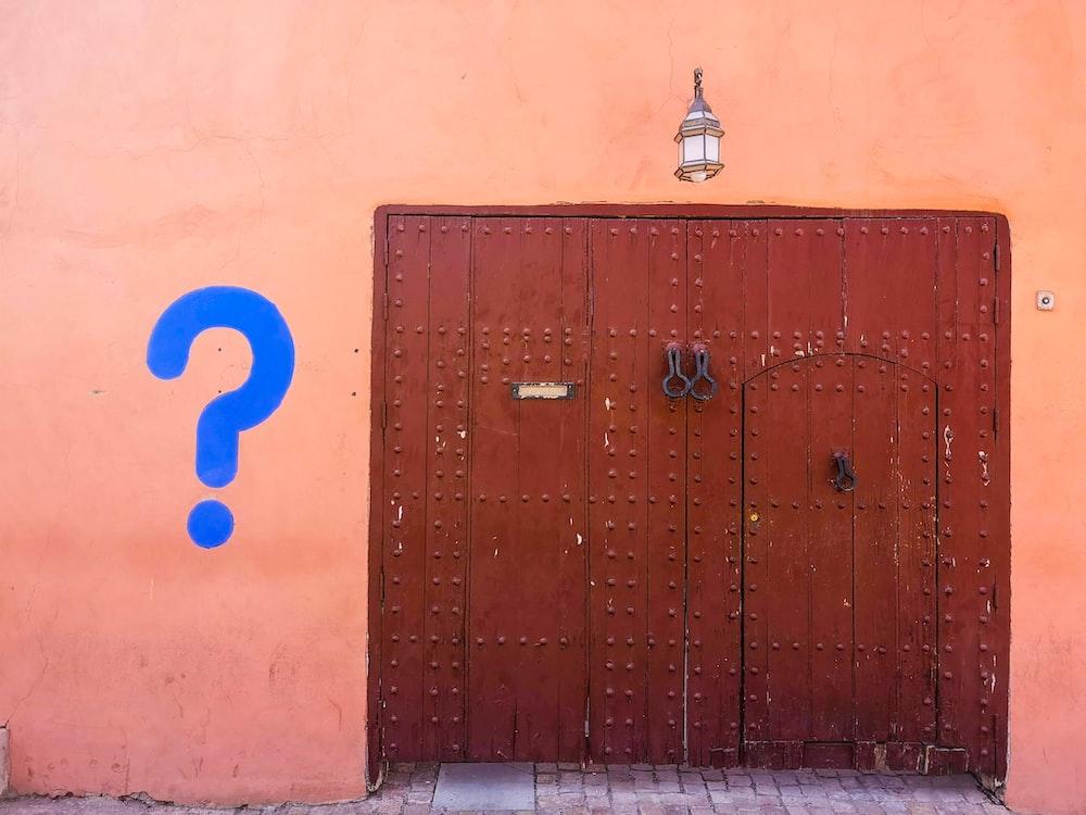 brown wooden door with blue number 8 print