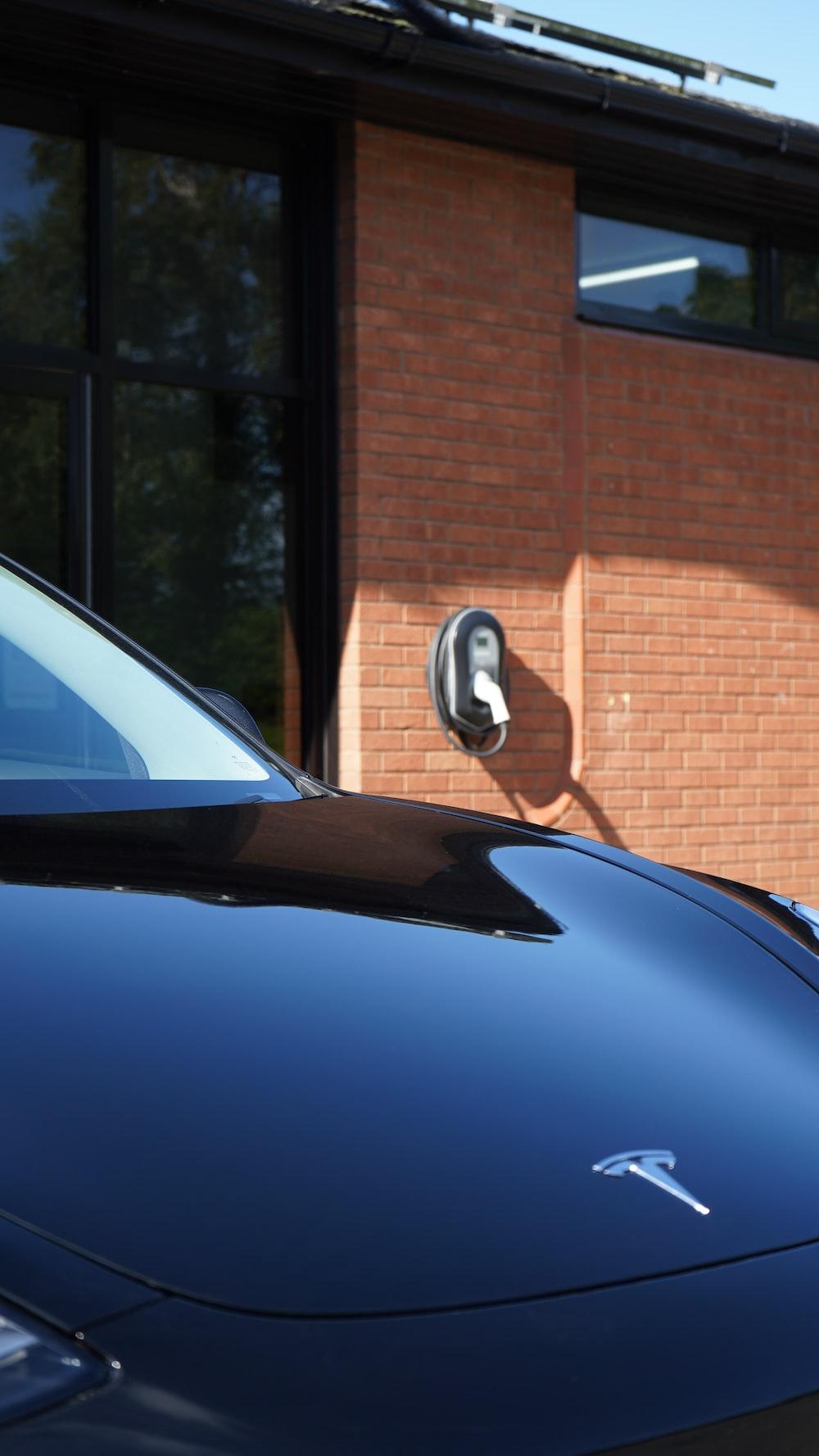 blue car parked near brown brick building