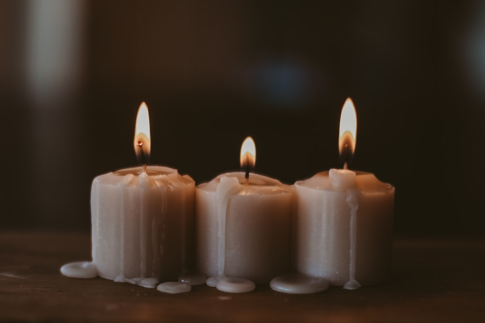 white candles on black surface