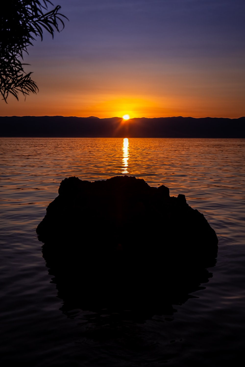 silhouette of rock on water during sunset