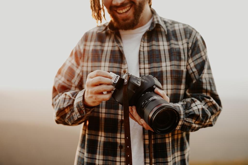 man in black and white plaid dress shirt holding black nikon dslr camera