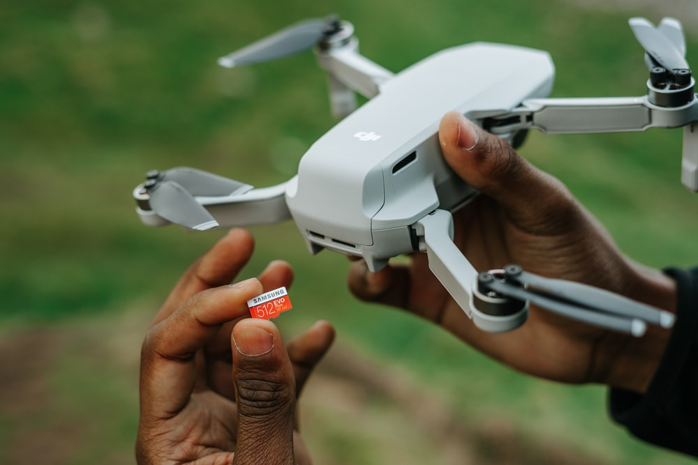 person holding white drone with red and white cards
