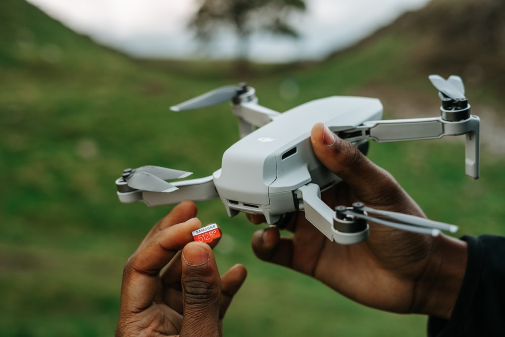 person holding white and gray drone