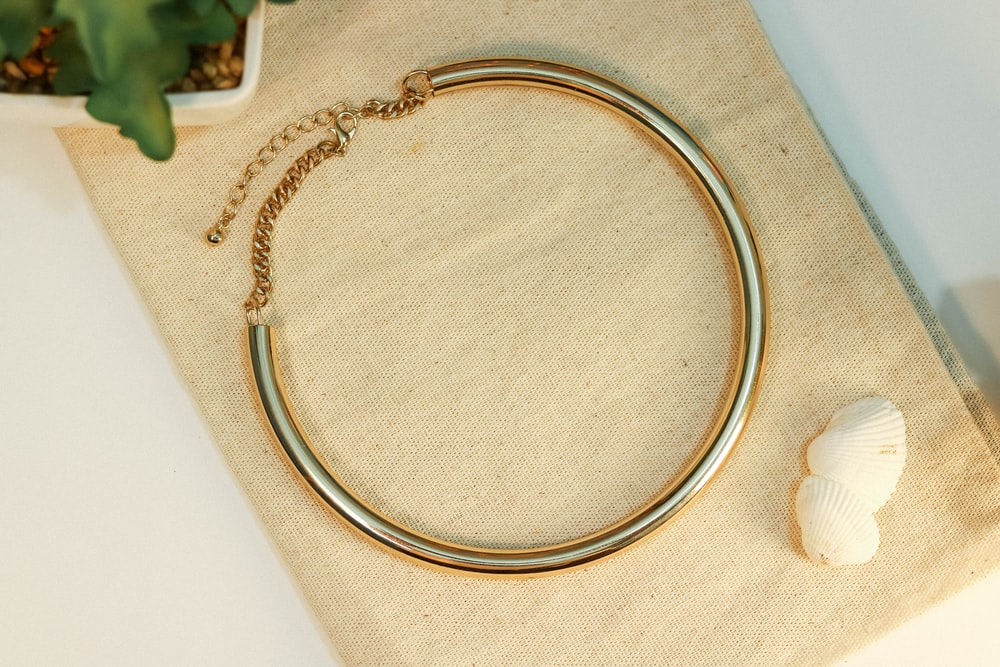 gold chain necklace on white textile