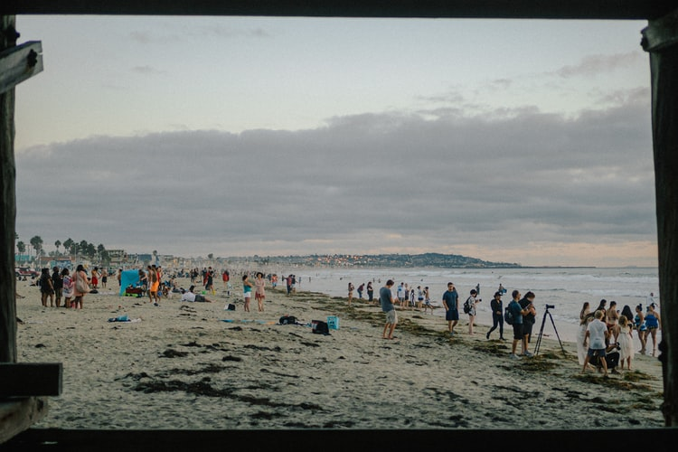 A photo of a beach. It looks like a colder day, there are people line up along the water looking out and some other people walking away. The image has a black frame.