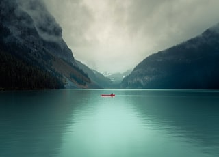 red boat on calm water near mountain during daytime