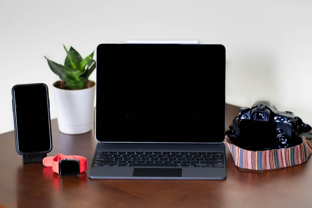 black and gray laptop computer beside red and black computer mouse