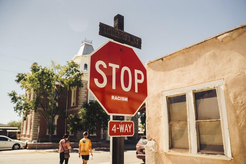 red stop sign near people walking on sidewalk during daytime