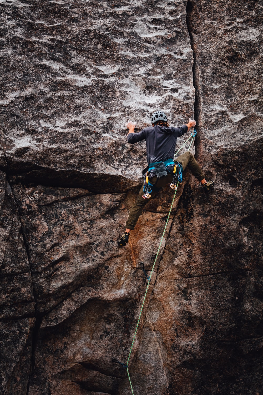 man in blue t-shirt climbing on brown rock during daytime