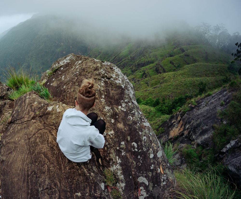 woman in white hoodie sitting on rock formation during daytime