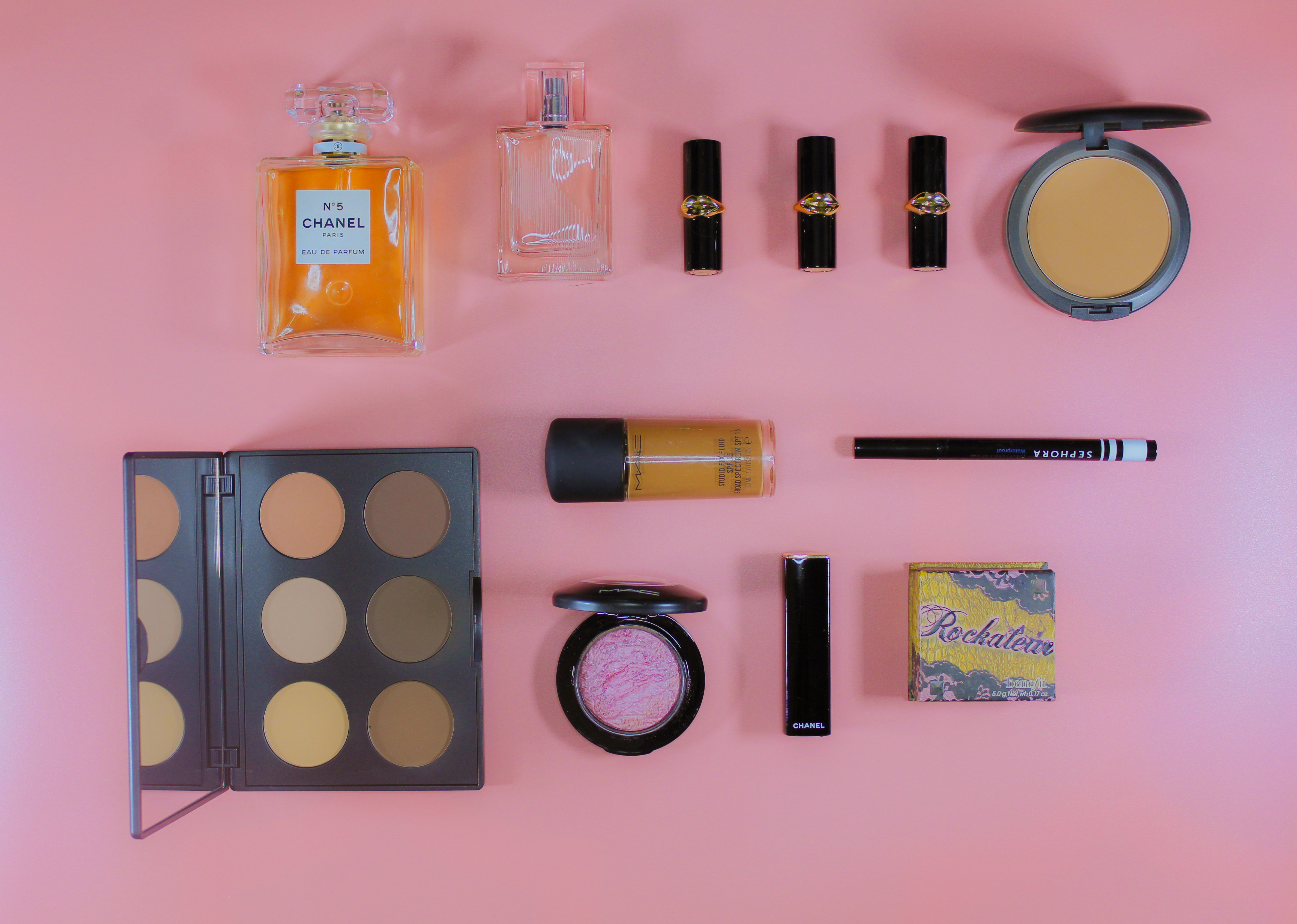 Flat lay featuring makeup and beauty items of a female traveler.