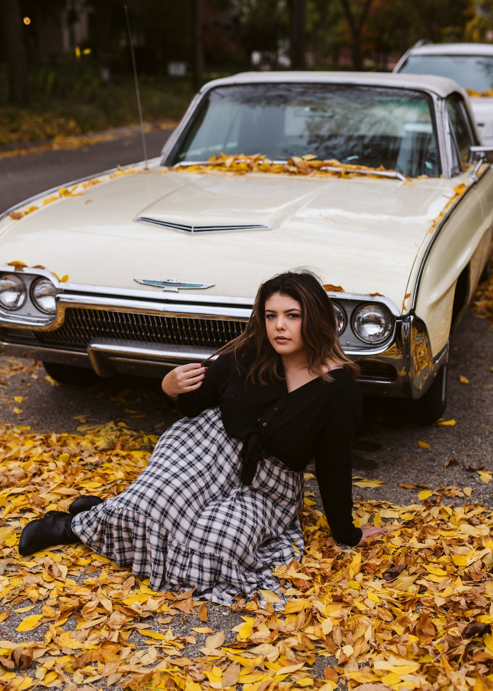 woman in black long sleeve shirt leaning on white car