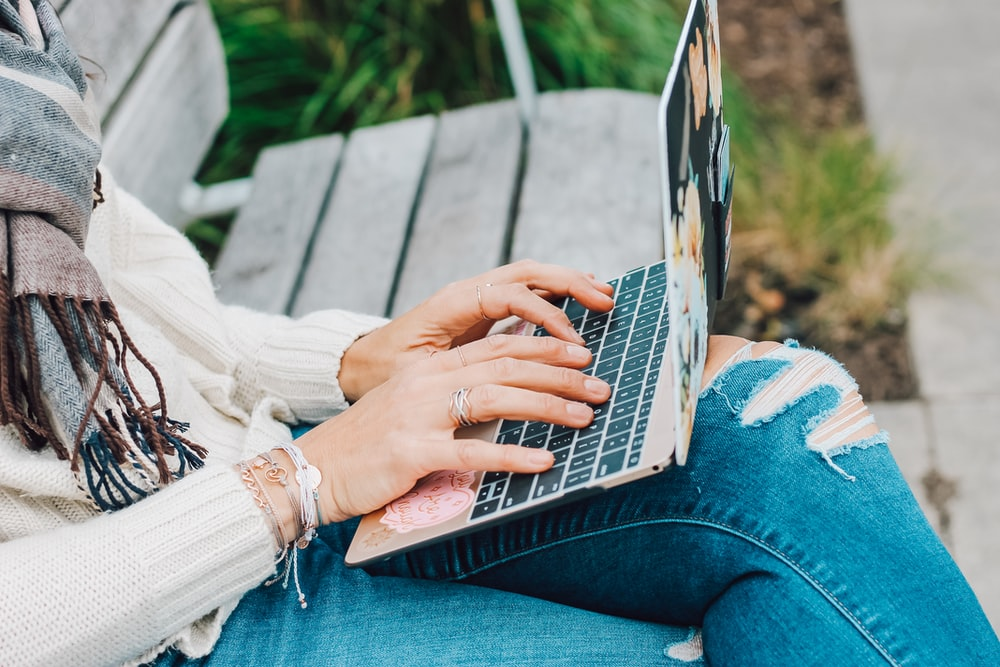 person in white long sleeve shirt and blue denim jeans using macbook pro