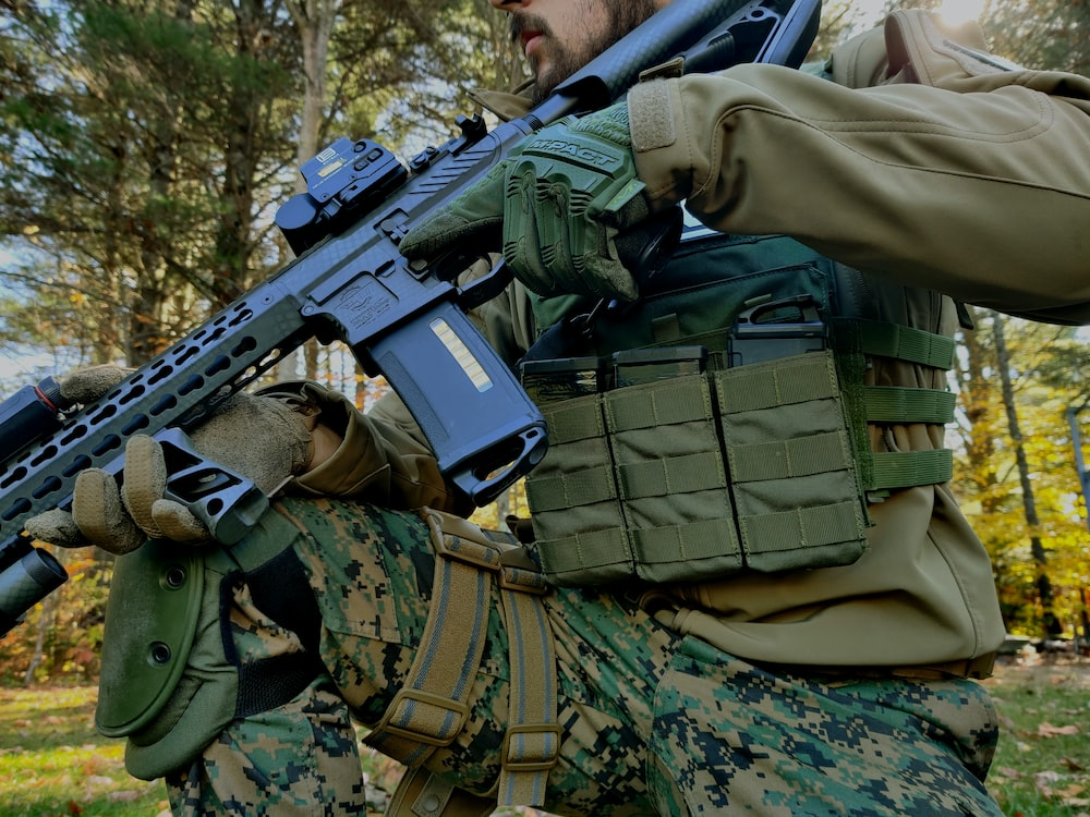 man in green and brown camouflage uniform holding black rifle