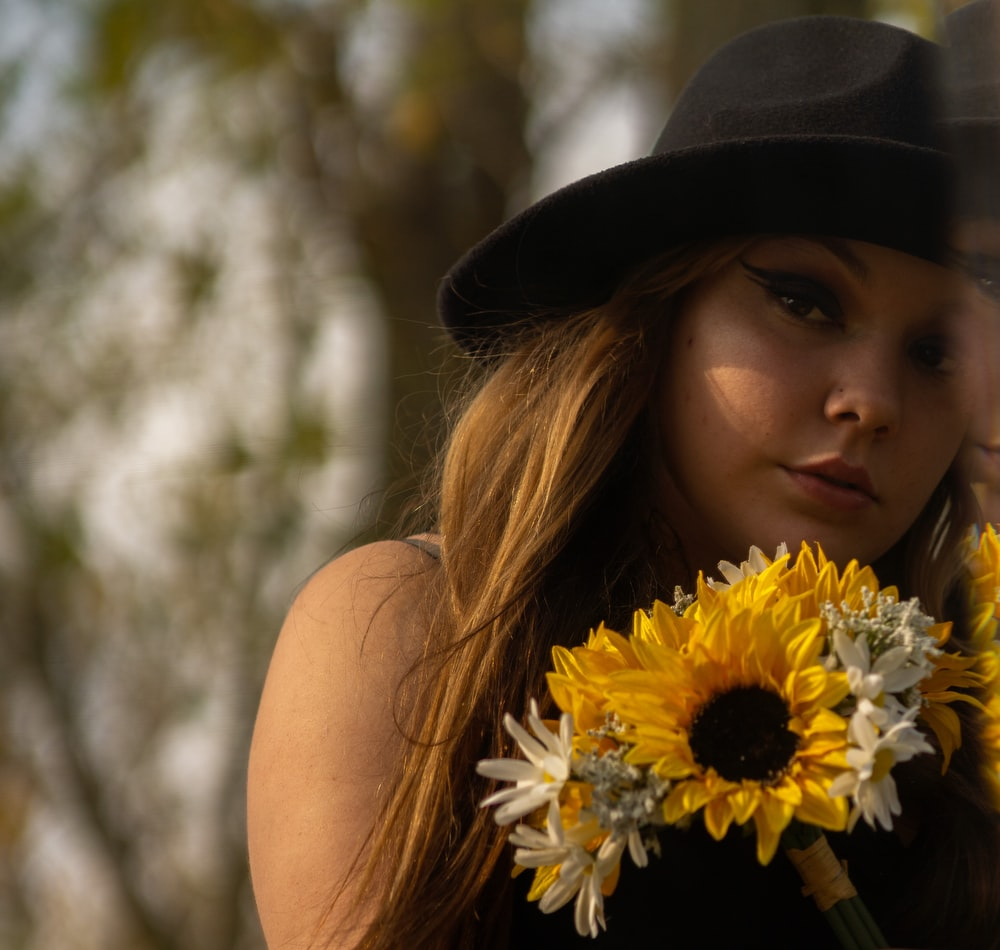 woman in black hat holding yellow sunflower
