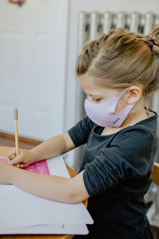 boy in black long sleeve shirt writing on pink paper