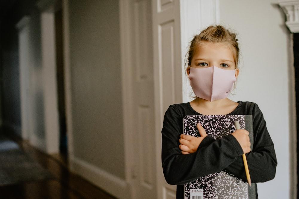woman in black cardigan wearing white mask