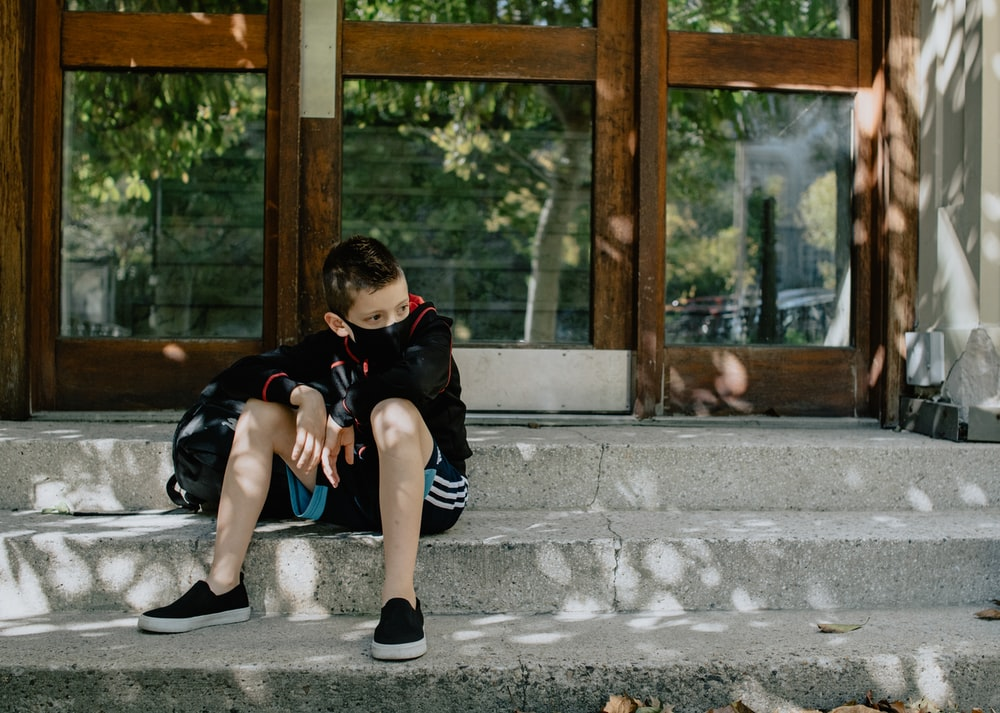 boy in black t-shirt and blue denim jeans sitting on concrete bench