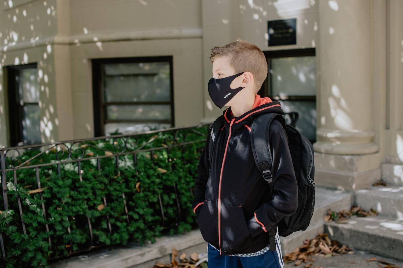 A boy wearing a black face mask
