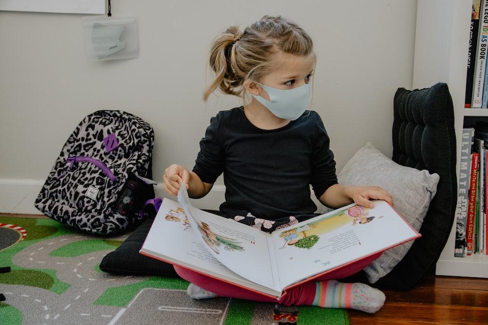 girl in black long sleeve shirt reading book