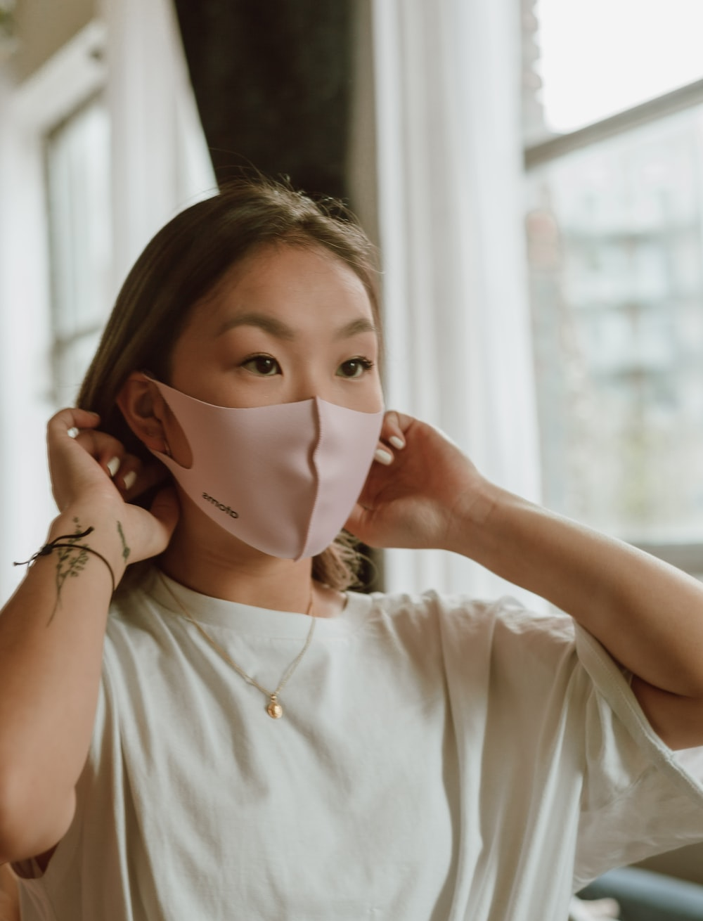 woman in white shirt covering her face with white mask
