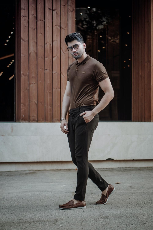 man in brown tank top and black pants standing near brown wooden door