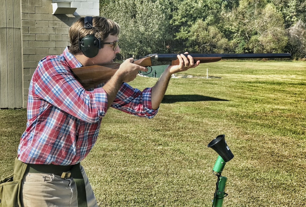 man in red blue and white plaid shirt and gray pants holding black and brown rifle