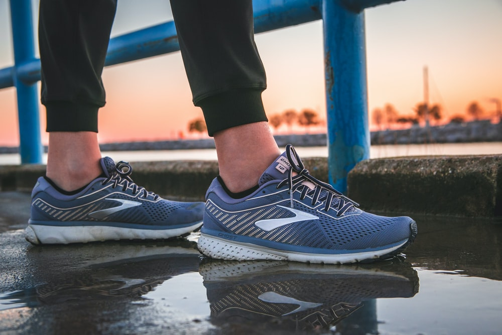 person wearing blue and white running shoes